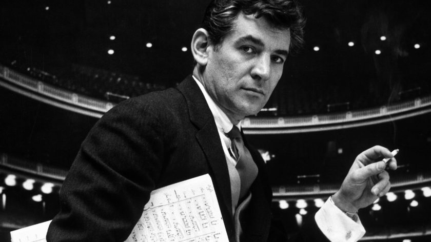36-year-old composer Leonard Bernstein, holding musical score with lighted auditorium behind him. He has written two symphonies, a song cycle, jazzy ballet Fancy Free, two Broadway shows (on the Town, Wonderful Town) and is preparing a musical of Candide.  (Photo by Gordon Parks//Time Life Pictures/Getty Images)